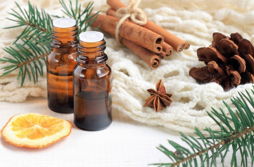 Essential oil surrounded by orange, cinnamon and conifers.
