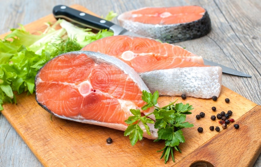 Salmon fillets in slices on a cutting board.