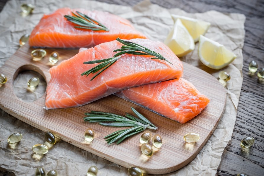 Three salmon fillets on a cutting board with omega-3 capsules and lemon wedges.