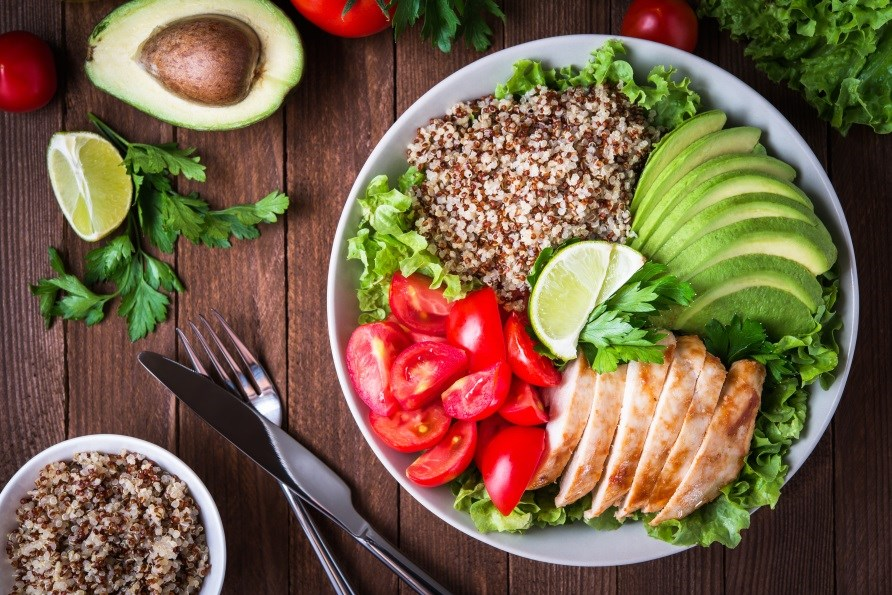 A meal with quinoa, vegetables, chicken and avocado.